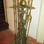 Kaminbesteck-Garnitur mit 4 Schürhaken um 1880, Messing-Bronze-Guss, 2 gekreuzte Gewehre an Ast mit Blättern gelehnt, gekrönt von einem Helm, reich florale Verzierungen, Breite: 55cm, Tiefe: 20cm, Höhe: 37cm - Preis: 280,-€
